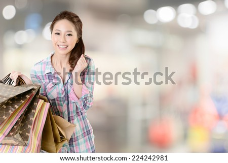 Exciting young shopping woman hold bags, closeup portrait with copyspace. - stock photo
