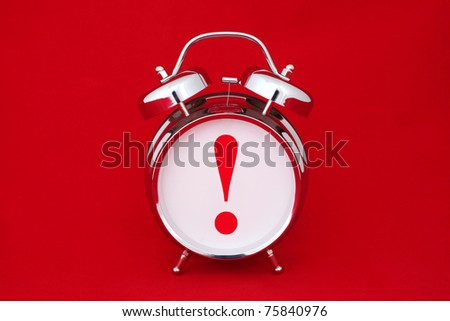 exclamation point on a alarm clock face. isolated on red - stock photo