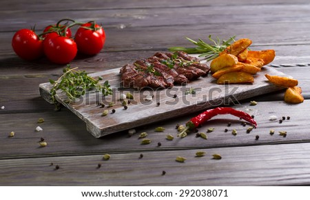 Exclusive dish. Grilled steak with fried potatoes and tomatoes. - stock photo