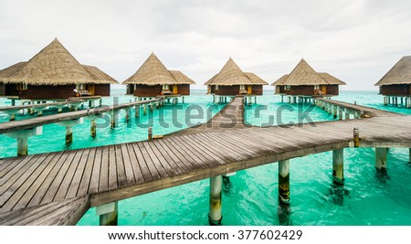 Exclusive luxury resorts pile houses floating on crystal clear turquise waters of ocean, Maldives - stock photo