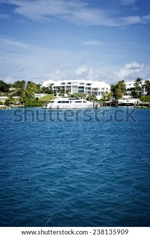 Exclusive yacht docked in front of luxurious houses in Paradise Island in the Bahamas - stock photo