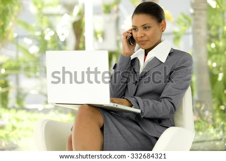 Executive Afro American woman using laptop on knees and giving a call will cell phone - stock photo