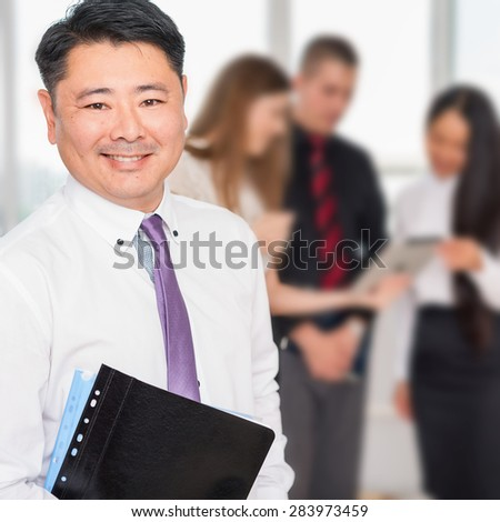 Executive asian boss or successful director with his business team at background. Multiracial people is a good addition for running a successful business - stock photo