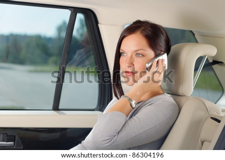 Executive attractive female manager sitting in car backseat calling phone