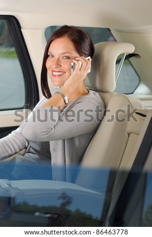 Executive attractive female manager sitting in car backseat calling phone - stock photo