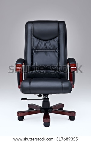 Executive black leather office chair over white ground with wooden handles and legs. - stock photo