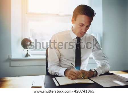 Executive business man working at office writing in a calendar and looking seriously - stock photo
