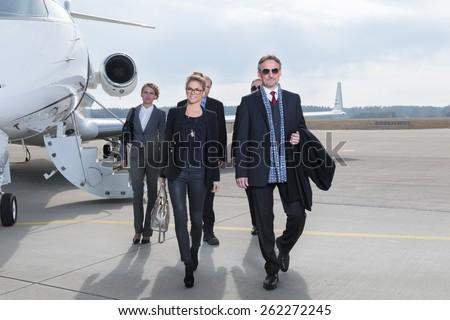 executive business team leaving corporate jet - stock photo
