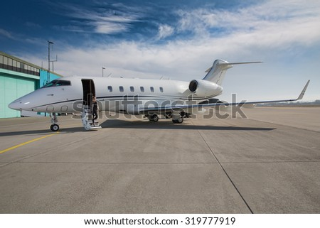 executive business woman leaving a corporate jet plane - stock photo