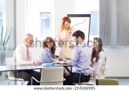 Executive business woman presenting her idea to colleagues at meeting. Teamwork. - stock photo