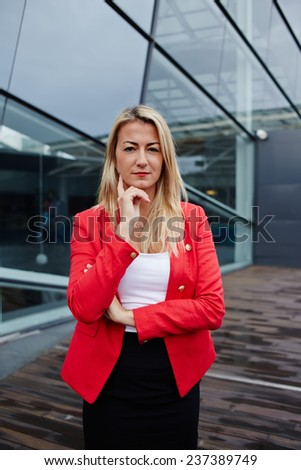 Executive business woman standing against office building looking reflectively to the camera, executive woman carefully listen to the employee, business woman in red jacket standing near office  - stock photo