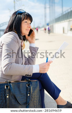 Executive business woman talking by mobile phone and read contract sitting on a park bench, focused on the job, spring mood - stock photo