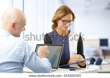 Executive business woman using clipboard while sitting at office and consulting together with colleague. - stock photo