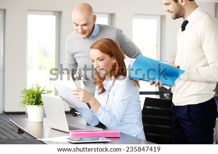 Executive business woman working on laptop while discussing problems with her team.  - stock photo