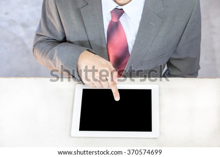 Executive businessman in suit touching and swiping in black blank empty tablet - ready to put any text or graphic onto screen - stock photo
