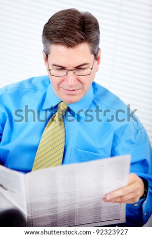 Executive businessman reading a newspaper. At a modern office.