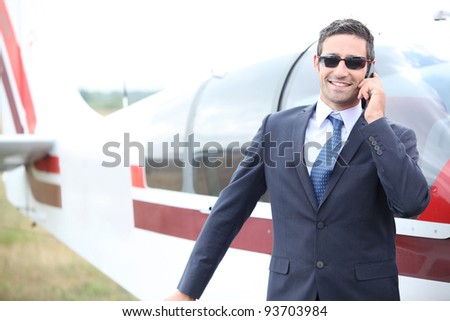 Executive chatting on the phone in front of a small aeroplane - stock photo