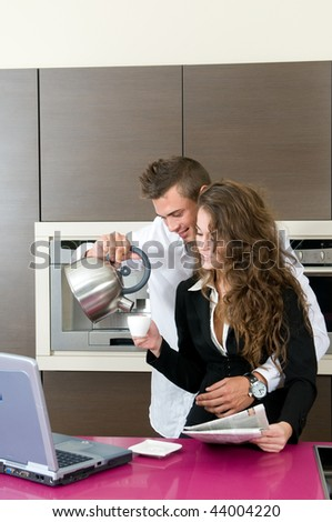 executive couple in kitchen with coffee looking at laptop computer