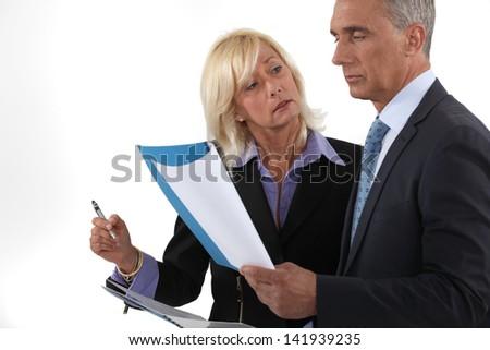 Executive couple looking through report - stock photo