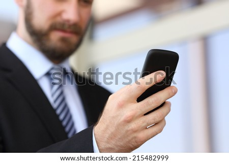 Executive hand using a smartphone in the street with an office building in the background - stock photo