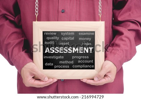 """Executive holding a hanging frame with """"ASSESSMENT"""" text - stock photo"""