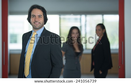 Executive in a suit looking at camera with two woman on the background