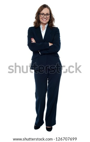 Executive in business attire standing arms folded, full length portrait.