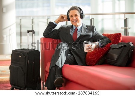 Executive man on business travel trip relaxes early for his flight - stock photo