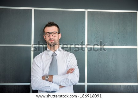 Executive man with glasses smiling standing in front of wall - stock photo
