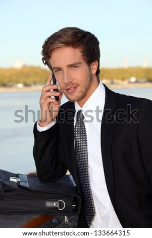 executive on the phone at a riverside - stock photo