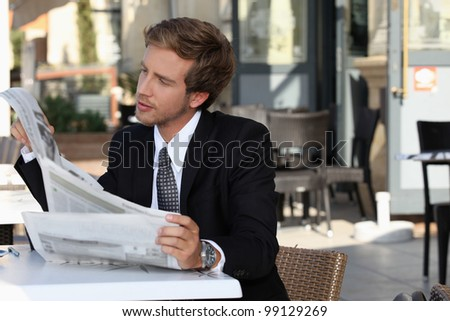 Executive reading a newspaper on the terrace - stock photo