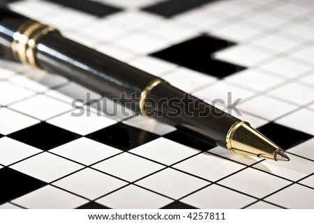 Executive's ballpoint pen on a blank crossword puzzle.  Conceptual image for filling in the blanks, problem solving, brain storming, etc. - stock photo