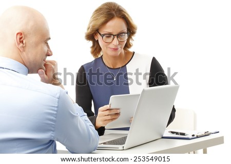 Executive sales woman discussing financial plan with sales man, while sitting at desk. Isolated on white background. - stock photo