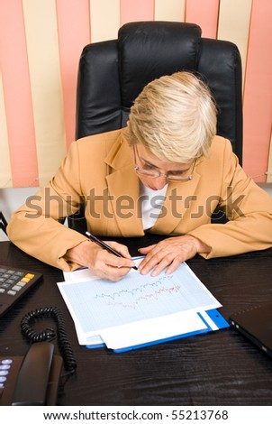 Executive senior woman financial analyst  writing on graphs