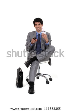 Executive sitting with telephone and refreshment - stock photo