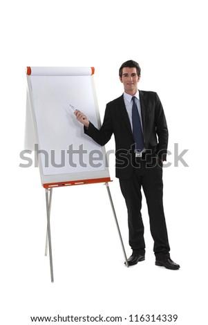 Executive standing next to a flipchart - stock photo