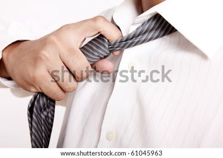 Executive taking off his tie. white shirt - stock photo
