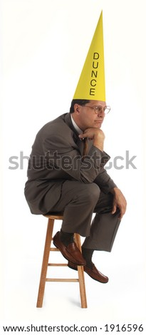 executive thinking on a stool, wearing a dunce hat on white background - stock photo