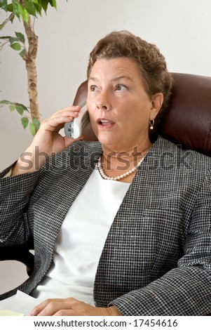 Executive type businesswoman gets a call with shocking or problematic news