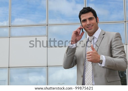 Executive using a cellphone outside and giving the thumbs up - stock photo