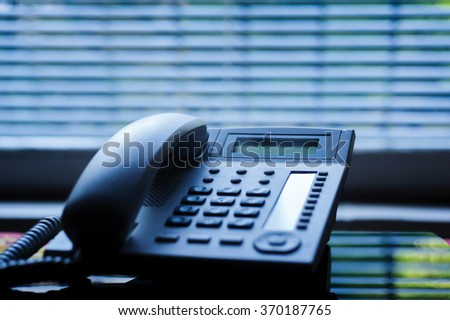 Executive VoIP desk phone with traditional corded headset and the business office window blinds in the background. Shallow depth of field - focus on the center of the phone - stock photo