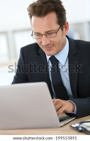 Executive with eyeglasses working on laptop - stock photo