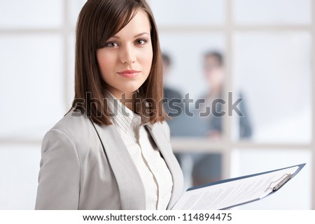 Executive with tablet on the glass wall background with people - stock photo