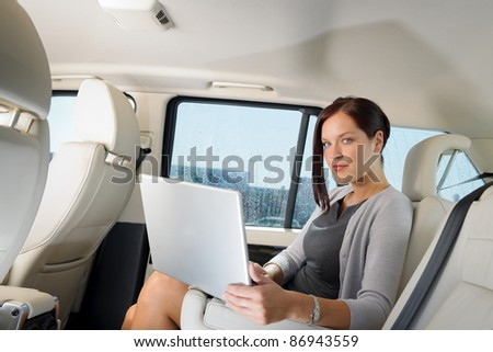 Executive woman manager working on laptop sitting car leather backseat - stock photo