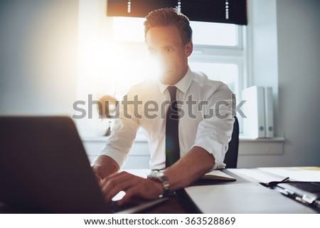 Executive working on laptop with documents on the desk - stock photo