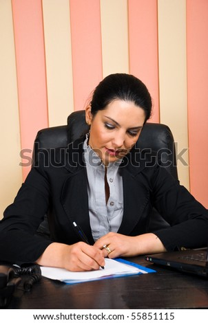 Executive young woman sitting at desktop in office and writing on papers