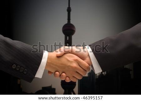 Executives handshake against a Asian background, Shanghai, China - stock photo