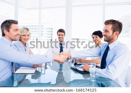 Executives shaking hands during business meeting at office desk - stock photo