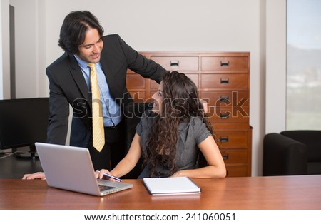 Executives working on computer and looking at each other - stock photo