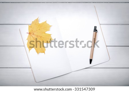 Exercise book with pen and autumn leaves on white boards. - stock photo